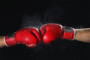 拳がぶつかり合っているボクシンググローブ